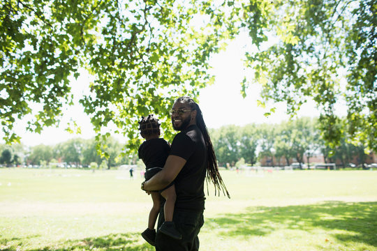 Portrait happy father with long braids carrying son in sunny park