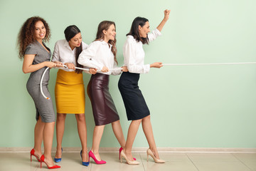 Young women pulling rope against color wall. Concept of feminism