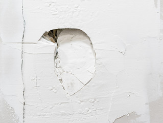 Large punched hole in wall. Close up. Recurrent drywall damage from door hitting the wall. Spackling compound applied with new damage visible. Aggressive and violent.