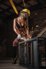 Young sexy beautiful girl works as grinder in workshop. Spectacular photo with sparks