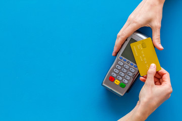 Contactless payment, paypass. Hand hold bank card near terminal on blue background top-down copy space