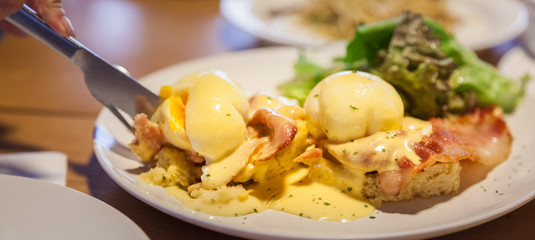 Selective Focused Eggs Benedict, sandwich consists of 2 halves of English muffin topped with poached egg, bacon or ham and hollandaise sauce. American breakfast or brunch dish. Morning meal concept