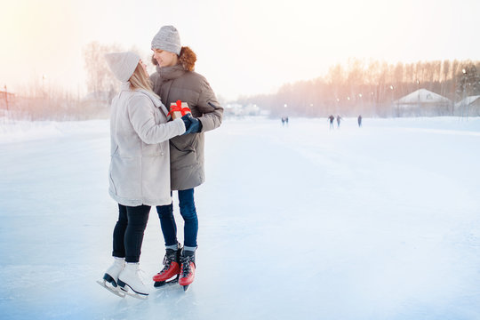 Man giving gift box girlfriend winter on ice rink, surprise romantic for Valentine Day or Christmas. Background snow sunset