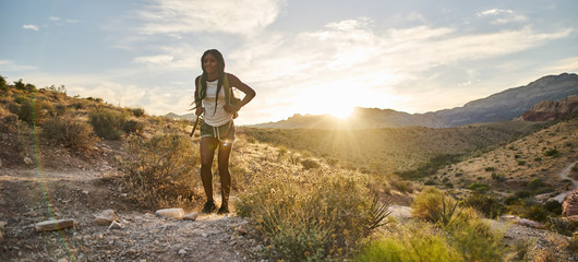 woman hiking at Red Rock Canyon during sunset with backpack Fotobehang