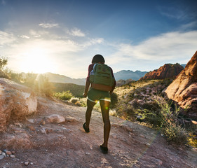 athletic african american woman hiking through red rock canyon in nevada at sunset