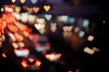 Heart-shaped Bokeh of lights from cars on the road at night.