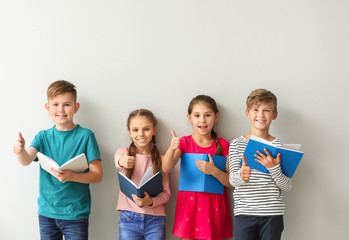 Cute little children with books showing thumb-up gesture on grey background