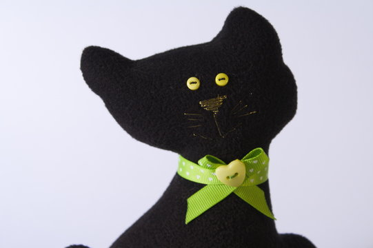 close up isolated soft toy of black cat with green collar. white background