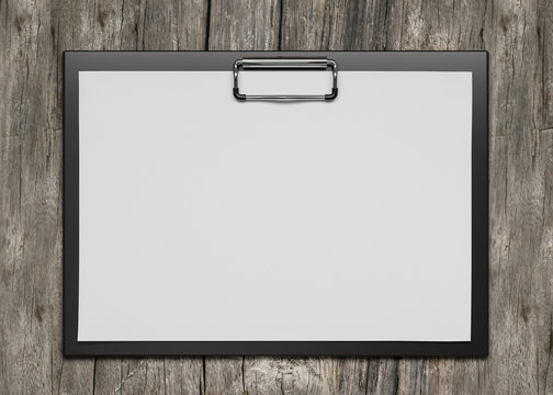 plastic clipboard with blank paper sheet isolated on wooden background 3d render illustration