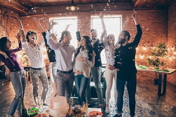 Photo of group amazing friends throwing confetti surprise baby party meeting future parents big cake champagne snacks on table formalwear restaurant indoors