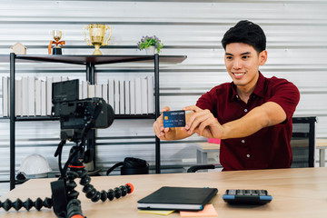 Smiling Asian male recording video selling stuff through social media and video platform showing credit card using camera sitting at table in house