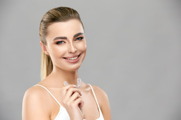 pretty girl with perfect smile holding invisible braces and smiling to camera on grey background