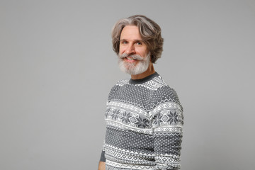 Smiling elderly gray-haired mustache bearded man in knitted sweater posing isolated on grey...