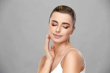beautiful girl with light make-up smiling with her eyes closed and touching her cheek on grey background