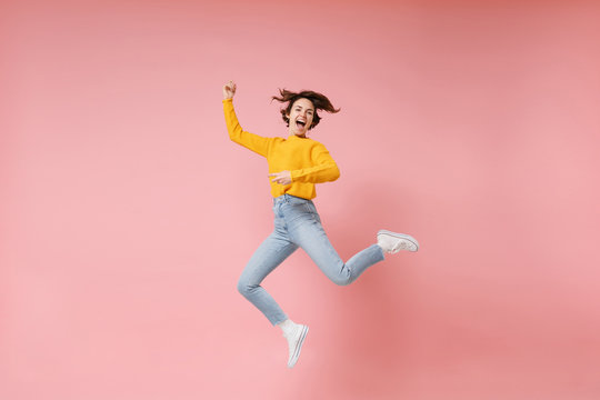 Excited young brunette woman girl in yellow sweater posing isolated on pastel pink background in studio. People lifestyle concept. Mock up copy space. Having fun fooling around, rising hands, jumping.