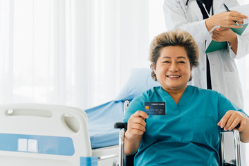 Pleased senior Asian lady in hospital attire smiling while sitting on wheelchair and demonstrating credit card in hospital ward
