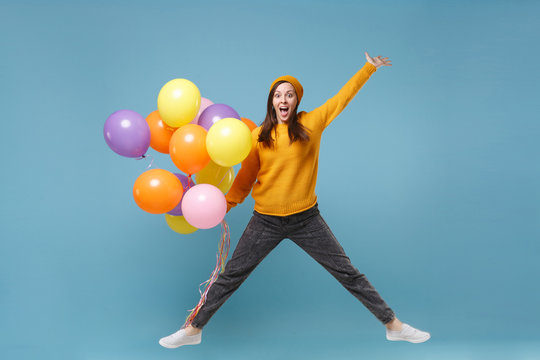 Surprised young woman girl in sweater and hat posing isolated on blue background. Birthday holiday party, people emotions concept. Mock up copy space. Celebrating hold colorful air balloons jumping.