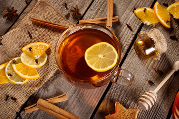 Poster de jardin The Cup of hot tea on rustic wooden plank with cinnamon stick, orange, lemon slices, honey, anise, cloves and other decoration. Vintage.