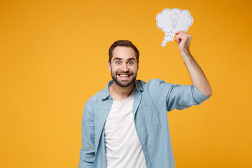 Smiling excited young man in casual blue shirt posing isolated on yellow orange wall background,...