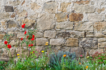 Background: Beautiful rustic medieval castle wall with colourful flowers in the foreground