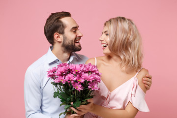 Funny young couple two guy girl in party outfit celebrating isolated on pastel pink background....
