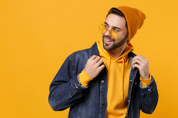 Handsome young hipster guy in fashion jeans denim clothes posing isolated on yellow orange...