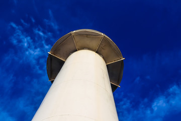 Lighthouse on the blue sky background, view from below