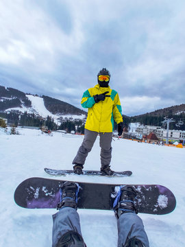 couple sitting at snowed hill with snowboard. winter activities