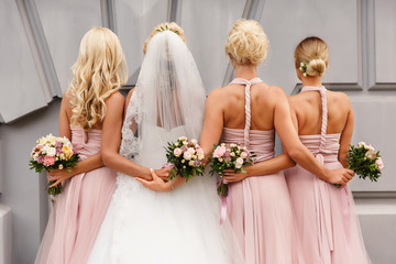 Bride and bridesmaids in pink dresses posing with bouquets at wedding day. Happy marriage and...