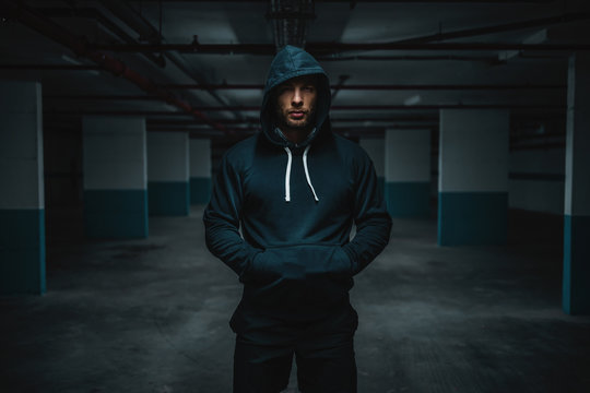 Serious attractive muscular caucasian sportsman in hoodie standing in underground garage with hands in pockets at night. Urban life concept.