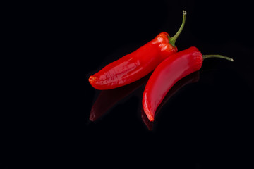Canvas Prints Hot chili peppers Fresh red chili peppers on black background. Two hot chili peppers. Spicy ingredient for cooking.