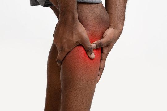Close up of young man massaging his painful leg