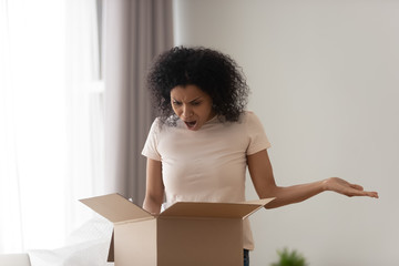 African woman unpacking parcel feels angry see damaged ordered goods