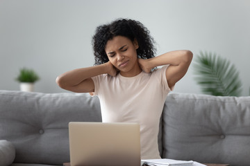 African woman having neck ache after long usage of computer
