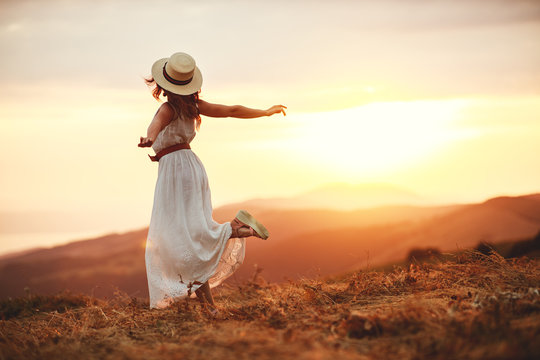 Happy woman standing with her back on sunset in nature