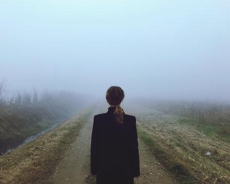 Una donna pensierosa nella nebbia nella ricerca di felicità