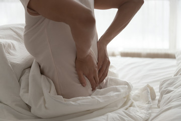 Closeup african woman touch lower back feels pain after sleeping
