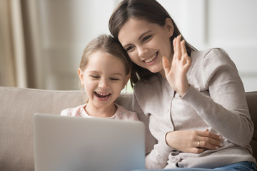 Happy mother and little daughter using laptop, making video call