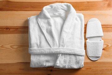 Clean folded bathrobe and slippers on wooden background, flat lay