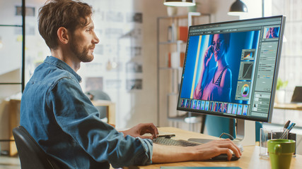 Beautiful Creative Male Video Editor with Beard and Jeans Shirt Works with Footage on His Personal Computer with Big Display. He Works in a Cool Bright Office Loft.
