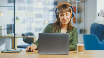 Young Beautiful Brunette Works on a Laptop Computer in Cool Creative Agency in a Loft Office. She is Wearing Headphones. She is Happy, Smiling and is Having Fun.