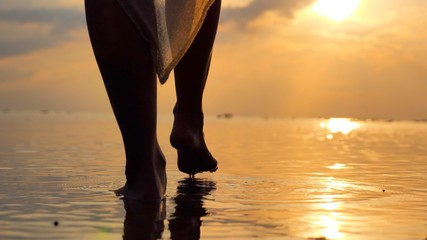 Close up at  foot of young woman walking in at seashore  wearing a long flowing dress as sunset time in the distance