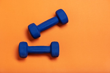Pair of blue dumbbells Isolated on orange background.