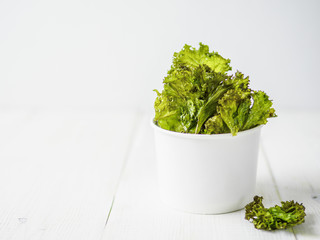 Kale Chips with salt in paper cup. Homemade healthy snack for low carb, keto, low calorie diet. White wooden background. Ready-to-eat kale chips, copy space for text. Banner