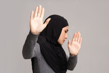 Afraid arabic girl showing stop gesture, protecting herself from violence