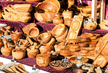 Handmade utensils, bowls, chopping board of olive wood on a outdoor stand.