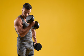 Strong bodybuilder working out with dumbbells