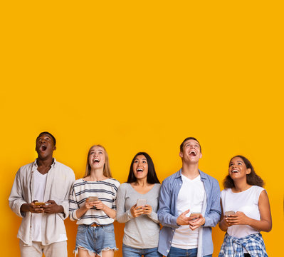 Group of surprised students with smartphones over yellow background