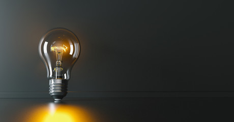 Illuminated light bulb leaning against a wall, concept for creativity, innovation and solution, copyspace for your individual text.