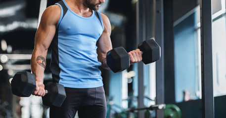 Muscular athlete picking up dumbbells at gym